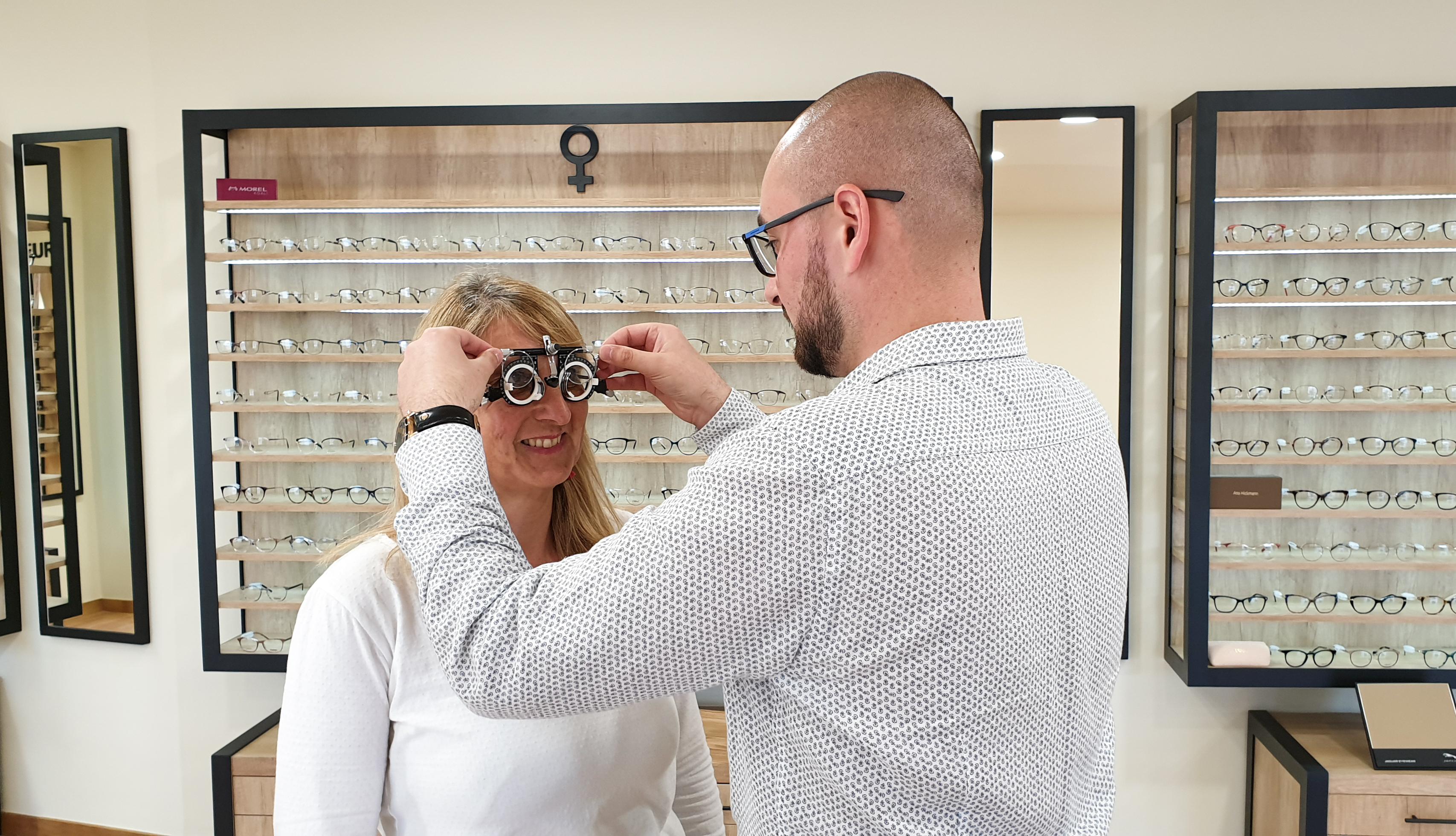 photo représentant l'opticien qui règle une lunette d'essai sur une dame